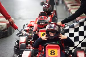Row of children in go-karts with helmets ready for a race